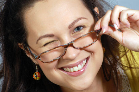 Portrait about smiling and winking woman in glasses with hand.
