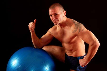 okay: The smiling man with pilates ball shows okay.