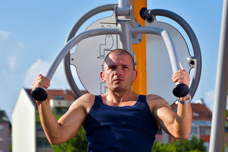 undershirt: The muscular man in undershirt is exercising outdoor on equipment.