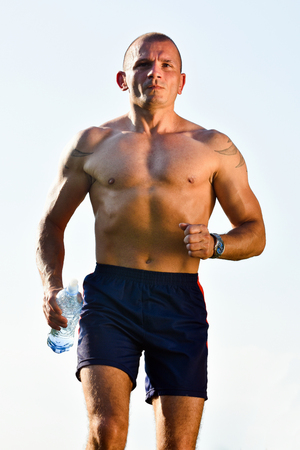 bottled water: The man is running with bottled water.