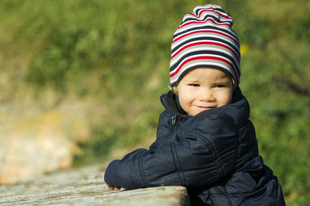 background green: Lovely little boy with striped cap is outdoor on green background.
