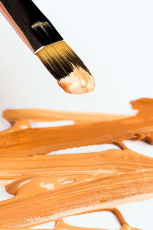 mixed colors: Brush for concealer with mixed colors is on white background.