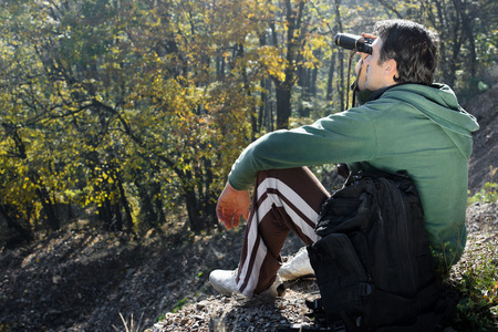 mountaineer: The mountaineer is looking at the nature with his binoculars. Stock Photo