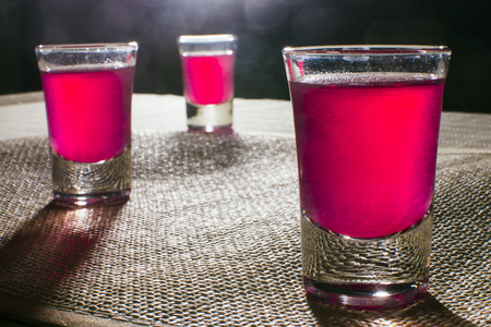 alcoholic drink: Three alcoholic glasses with pink alcoholic drink.