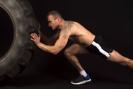 pushes: The sportsman pushes a big tractor tire on black background. Stock Photo