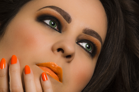 eyes green: Beauty portrait about woman with green eyes and orange perfect makeup.