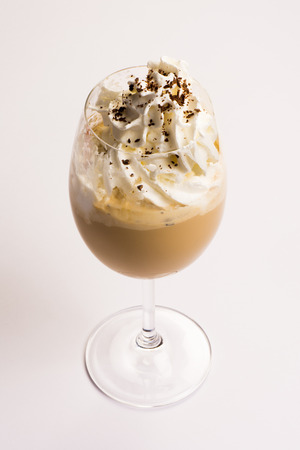 Coffee with whipped cream and chocolate on white background.