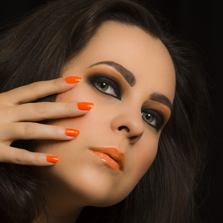 eyes green: Retrato de la belleza sobre la mujer con los ojos verdes y el maquillaje de color naranja. Foto de archivo