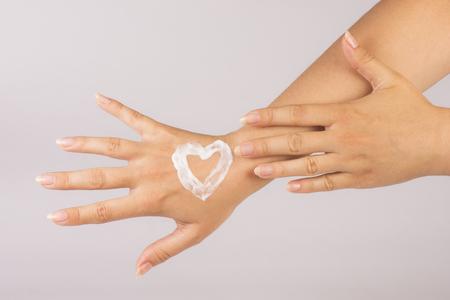 Heart shape from hand cream on hand.