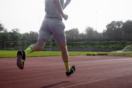 quickness: The runner is running at the stadium. Stock Photo
