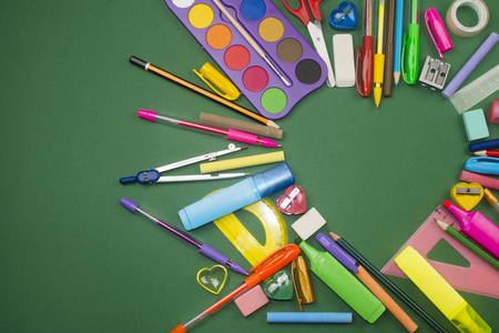 crayon  scissors: Different school supplies are in heart shape on green background.
