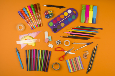 crayon  scissors: Different school supplies are on orange background.