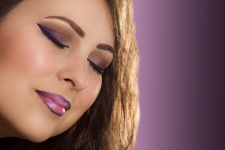 ojos cerrados: Beauty portrait about woman with closed eyes and purple make up on purple background.