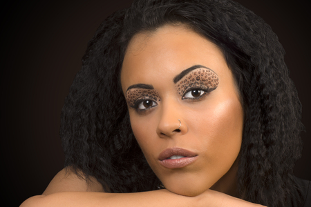 woman shadow: Beauty portrait about black woman with animal print eye shadow. Stock Photo