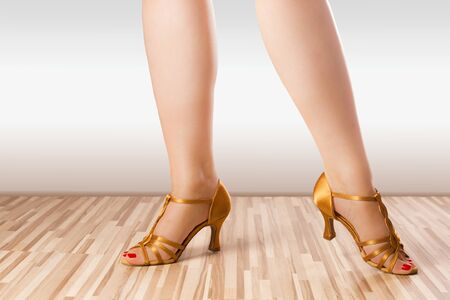 latino dance: Female legs are posing in golden latino dance shoes. Stock Photo