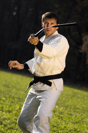 Kungfu expert in white kimono with black belt is practicing with nunchaku outdoors.
