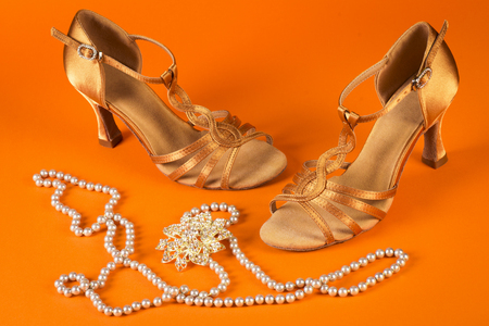 baile latino: Latin dance shoes with pearls accessories on orange background. Foto de archivo
