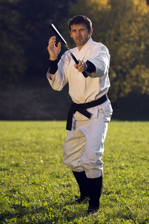Ninja in white kimono is practicing with nunchaku outdoors in the park.