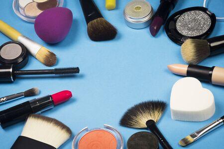 Verschiedene Make-up-Produkte sind auf blauem Hintergrund.