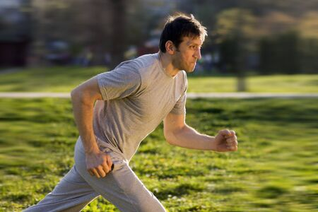 The man is running outdoors at the park. Stock Photo