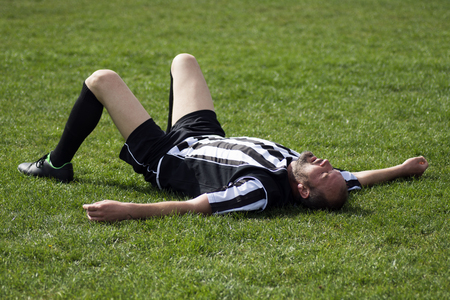 The tired soccer player is lying down on the grass on playing field, finished football match.