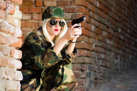 The female soldier with blond hair is holding gun on brick wall.