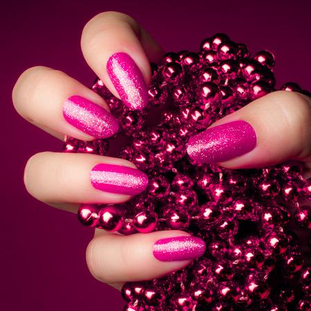 보라색 배경에 핑크 진주 보석으로 반짝이 핑크 손톱. 매니큐어와 네일 케어 개념입니다.