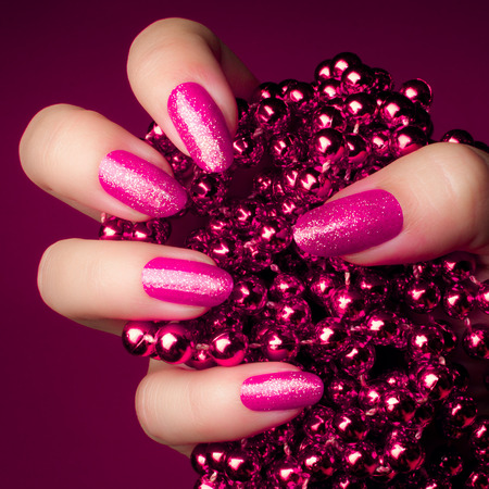 Shiny glittering pink nails with pink pearl jewel on purple background. Manicure and nail care concept. Foto de archivo