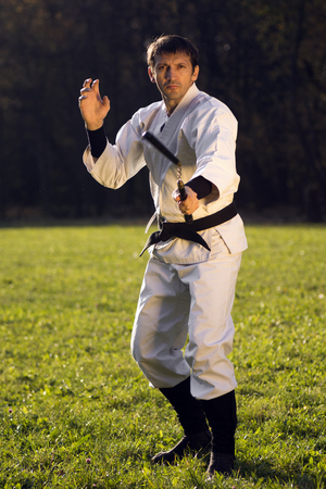 Man in white kimono is practicing with nunchaku outdoors in the park. Stock Photo