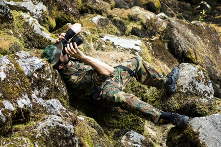 The man is lying down on rocks and discovering environment in nature with binoculars.