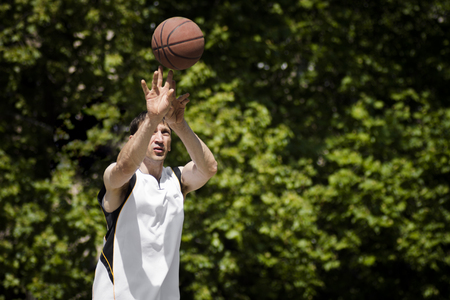 The basketball player is throwing the basketball ball outdoors on green background. Stock Photo