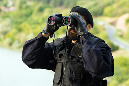 The security man in uniform is looking away with binoculars outdoor in nature. Фото со стока