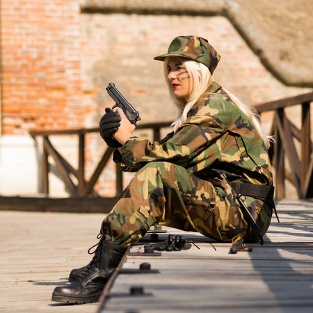 The woman in military uniform with gun in hands is sitting outdoors. Stock Photo
