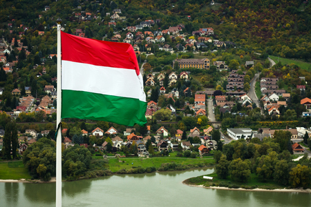 The Hungarian flag is outdoors in Visegrad town in Hungary on village background.