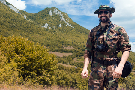 The smiling military man or soldier in military uniform with camera is outdoors in nature on mountain background.