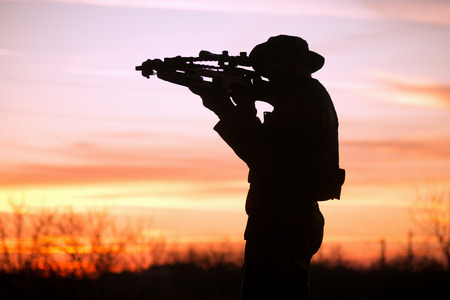 The soldier or hunter is aiming with cross-bow at sunset in nature, silhouette.