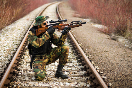 The soldier or hunter in military uniform is aiming with cross-bow on railway outdoors in nature.
