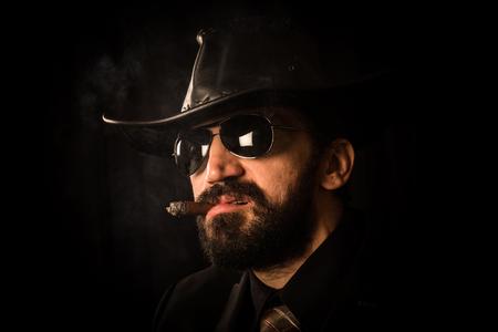 Portrait of elegant man in suit with black cowboy hat is smoking cigar on black background. Clint Eastwood style. Reklamní fotografie