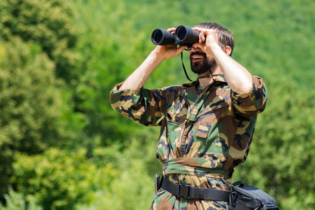 The smiling man in military uniform is watching with binoculars in nature on greenery background.