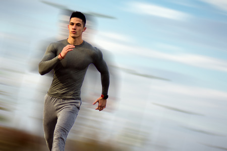 The handsome sportsman is running at high speed at the street outdoors.