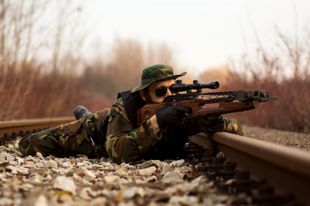 The military man is lying down on railway and aiming with crossbow weapon to target outdoors. Stock Photo