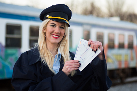 The smiling female railway worker or railroad employee is showing the tickets outdoors on railway station.