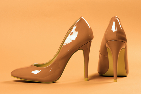 Sexy beige high heels shoes are on beige background.