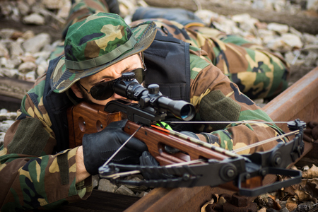 The military man is aiming with crossbow weapon and lying down on railway track. Stock Photo