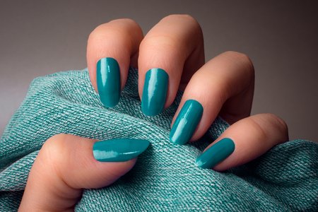 The female hand with turquoise nails is holding turquoise colored denim textile on gray background. Manicure concept.