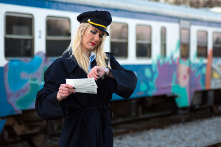 The blond hair female railroad employee or railway worker is checking time on her watch and holding two tickets, waiting for train.