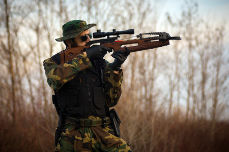 The military man is shooting with crossbow weapon outdoors. Stock Photo