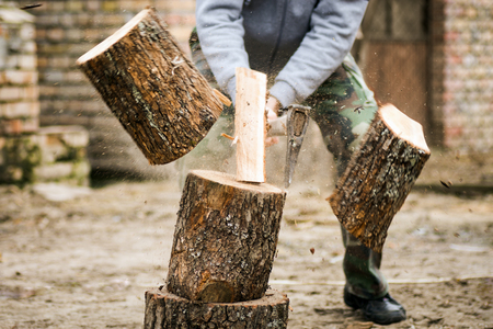 The lumberjack is cutting wood or firewood with axe outdoors. Banco de Imagens