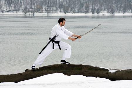 The ninja in white kimono with sword is practicing martial arts on wood on riverside at winter. Stock Photo