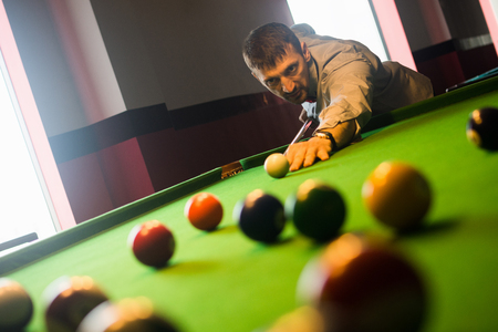 The player is concentrate to play billiards and to shoot the billiard balls in billiard club.